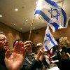 Jerry McCurry, of Luther, Okla., who is director of a group called Christians United for Israel, waves an Israeli flag during a song before a Community Gathering at Temple B\'nai Israel in Oklahoma City on Monday, Jan. 12, 2009. By John Clanton, The Oklahoman