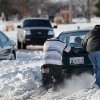 Two men push a small car through snow ruts on Britton Road. Many spent Christmas Day, Dec. 25, 2009, digging out from record snow storm that dumped 14 inches of snow in the Oklahoma City area. Photo by Jim Beckel, The Oklahoman