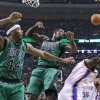 Photo - A loose rebound bounces away from Boston Celtics forwards Chris Wilcox (44) and Brandon Bass (30) as they vie under the boards with Oklahoma City Thunder center Kendrick Perkins, right, during the first half of an NBA basketball game in Boston, Friday, Nov. 23, 2012. (AP Photo/Elise Amendola)