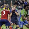 Photo - Chivas USA goalkeeper Dan Kennedy, middle, reacts with Carlos Bocanegra (3) as Seattle Sounders FC forward Obafemi Martins, right, celebrates Lamar Neagle's goal during first half a MLS soccer match Saturday, April 19, 2014, in Carson, Calif. (AP Photo/Chris Carlson)