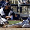 San Diego Padres\' Rico Noel, right, slides safely past Milwaukee Brewers catcher Jonathan Lucroy for an inside-the-park home run during an exhibition spring training baseball game on Friday, March 7, 2014, in Phoenix. (AP Photo/Morry Gash)