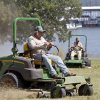 Photo - State employees Oddie Dean and Tony Palmer mow Wednesday at Lake Thunderbird in Norman. More than 400,000 Oklahomans are expected to travel over the weekend.  Photo by Steve Sisney, The Oklahoman <strong>Steve Sisney - STEVE SISNEY</strong>