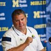 Photo - FILE - In this Aug. 10, 2014, file photo, Michigan head coach Brady Hoke answers questions from the media during a news conference at the NCAA college football team's preseason media day in Ann Arbor, Mich. Coaches often say they are always on the hot seat. That might be true, but some seats are hotter than others. A few coaches in high-profile positions heading into 2014 very much in need of winning records and quality victories. (AP Photo/Tony Ding, File)