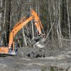 An excavator dislodges and stacks logs buried in deep mud at the scene of a deadly mudslide Wednesday, April 2, 2014, in Oso, Wash. Officials have so far confirmed the deaths of 29 people, although only 22 have been officially identified in information released Wednesday morning by the Snohomish County medical examiner\'s office. (AP Photo/Elaine Thompson)
