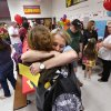 Kindergarten teacher Erin Baxter hugs a parent while others visit around them. There was lots of hugging and plenty of joy at Eastlake Elementary School on SW 134, when Eastlake School hosted a reunion of students, parents, teachers and families from Plaza Towers Elementary School on Thursday, May 23, 2013. Seven students died at Plaza Towers School in Monday\'s EF-5 tornado, which also destroyed the school. Photo by Jim Beckel, The Oklahoman.