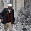 Photo - This Tuesday, March. 18, 2014 photo provided by the anti-government activist group Aleppo Media Center (AMC), which has been authenticated based on its contents and other AP reporting, a Syrian man, injured by a government airstrike, walks outside a damaged building in Aleppo, Syria. Activists said Syrian warplanes and helicopter gunships carried out several air raids in the northern province of Aleppo on Tuesday killing and wounding a number of people. (AP Photo/Aleppo Media Center, AMC)