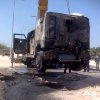 Photo - The charred remains of an armored vehicle are loaded onto a trick after a rocket-propelled grenade attack on a police checkpoint that killed a police colonel in El-Arish, Egypt, Friday, July 12, 2013. Officials say the attack happened early on Friday south the city of El-Arish when militants fired an RPG at an armored car at the checkpoint, killing 40-year-old Lt. Col. Ahmed Mahmoud. Islamic extremists have intensified attacks in Egypt's Sinai Peninsula after the ouster of President Mohammed Morsi, striking almost daily against the military and security forces, as well as targeting minority Christians. The violence raises the possibility of a military move, and the region's Bedouin residents are fearing an increase in instability. (AP Photo/Muhammed Sabry)