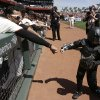 Photo - Miles Scott, right, dressed as Batkid, is greeted by San Francisco Giants left fielder Michael Morse after throwing the ceremonial first pitch before the Giants' home-opener baseball game against the Arizona Diamondbacks in San Francisco, Tuesday, April 8, 2014. On Nov. 15, 2013, Miles a Northern California boy with leukemia, fought villains and rescued a damsel in distress whiled dressed as a caped crusader through The Greater Bay Area Make-A-Wish Foundation. (AP Photo/Eric Risberg, Pool)