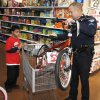 Curtis Westbrook, 11, watches as Sgt. Bill Gilbert with the Edmond Police Department loads a bike for him during the Shop With A Cop program at the Wal-Mart Supercenter at 15th and I-35 in Edmond Sunday, Dec. 14, 2008. PHOTO BY DOUG HOKE, THE OKLAHOMAN