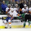 New York Islanders center Frans Nielsen, left, of Denmark, attempts to reach a loose puck as Dallas Stars\' Jordie Benn, right, defends in the second period of an NHL hockey game, Sunday, Jan. 12, 2014, in Dallas. (AP Photo/Tony Gutierrez)