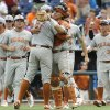 Photo - Texas catcher Tres Barrera (1) hugs Texas pitcher Travis Duke (27) after the last out against Louisville in an NCAA baseball College World Series elimination game in Omaha, Neb., Monday, June 16, 2014. Texas won 4-1. (AP Photo/Eric Francis)