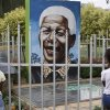 Children look through a fence at a portrait of former president Nelson Mandela in a Park in Soweto, South Africa, Thursday, March, 28, 2013. 94-year-old Mandela, the anti-apartheid leader who became South Africa\'s first black president, has been hit by a lung infection again and is in a hospital, the presidency said. Mandela, has become increasingly frail in recent years and has been hospitalized several times in recent months, including earlier this month when he underwent what authorities said was a scheduled medical test. The Nobel laureate is a revered figure in South Africa, which has honored his legacy of reconciliation by naming buildings and other places after him and printing his image on national banknotes. (AP Photo/Denis Farrell)