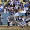 Colorado Rockies\' Josh Rutledge, left, hits a three-run home run as Los Angeles Dodgers catcher Tim Federowicz looks on during the sixth inning of a baseball game, Sunday, April 27, 2014, in Los Angeles. (AP Photo/Mark J. Terrill)
