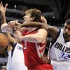 Photo - Houston Rockets center Omer Asik (3) is pressured under the basket by Dallas Mavericks center Chris Kaman, left, and guard O.J. Mayo (32) during the first half of an NBA basketball game, Wednesday, Jan. 16, 2013, in Dallas. (AP Photo/John F. Rhodes)