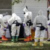 Photo - Federal agents wearing hazardous material suits and breathing apparatus inspect the trash can outside the West Hills Subdivision house of Paul Kevin Curtis in Corinth, Miss., Friday, April 19, 2013. Curtis is in custody under the suspicion of sending letters covered in ricin to the U.S. President Barack Obama and U.S. Sen. Roger Wicker, R-Miss. (AP Photo/Rogelio V. Solis)