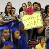 Marybell Zuniga, middle, holds her daughter, April Zuniga, 2, and a sign for her graduating sister, Claudia Zuniga, as her father, Jose Zuniga, looks on during the graduation ceremony for Emerson High School at the Oklahoma City campus of Langston University, Thursday, May 16, 2013. Emerson is an alternative education high school for students who need non-traditional learning because of a variety of reasons including teen pregnancy, homelessness and a need to work to support family. Photo by Nate Billings, The Oklahoman