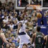 Dallas Mavericks\' Bernard James, center, dunks as Milwaukee Bucks\' Ersan Ilyasova, left, and Larry Sanders (8) watch in the first half of an NBA basketball game Tuesday, Feb. 26, 2013, in Dallas. (AP Photo/Tony Gutierrez)