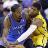 Photo - Indiana Pacers forward Paul George, right, attempts to knock the ball away from Oklahoma City Thunder forward Kevin Durant in the second half of an NBA basketball game in Indianapolis, Sunday, April 13, 2014. The Pacers defeated the Thunder 102-97. (AP Photo/Michael Conroy)