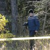 A State Police officer gathers photographic evidence in a wooded area at the corner of Pickard and Coldwater just west of Mt. Pleasant, Mich. on Thursday, Nov. 1, 2012 where a female body was found. John D. White, a 55-year-old ex-convict has confessed to beating and strangling a 24-year-old neighbor as part of a sexual fantasy, hiding her naked body and then returning to her central Michigan trailer home and helping her 3-year-old son get costumed for Halloween, authorities said Thursday.(AP Photo/The Morning Sun, Lisa Yanick-Jonaitis)