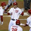 Washington Nationals\' Ryan Zimmerman, center, high-fives teammates Adam LaRoche, left, Michael Morse and Bryce Harper after hitting a two-run home run in the first inning of Game 5 of the National League division baseball series against the St. Louis Cardinals on Friday, Oct. 12, 2012, in Washington. Harper scored on the homer. (AP Photo/Nick Wass)