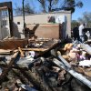 Residents and neighbors salvage items from the debris of a home that was damaged by severe weather that struck the prior evening, on Jefferson Avenue in Century, Fla., Tuesday, Feb. 16, 2016. (AP Photo/Michael Snyder)