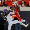 Oklahoma State\'s Josh Stewart (5) makes a catch over TCU\'s Chris Hackett (1) on a pass from Charlie Moore (not pictured) in the fourth quarter during a college football game between the Oklahoma State University Cowboys (OSU) and the Texas Christian University Horned Frogs (TCU) at Boone Pickens Stadium in Stillwater, Okla., Saturday, Oct. 19, 2013. OSU won, 24-10. Photo by Nate Billings, The Oklahoman
