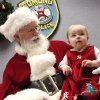 Santa stopped by the Edmond police station Saturday, Dec. 22, 2012, to visit with children, hear their Christmas lists and pose for keepsake photos that were provided for the children by Edmond police department. Posing on his lap is Clara Dunn, 10 months old. Playing Santa is Boyd Mize, a retired detective with the Edmond police department. This is the eighth year Mize has donned the Santa suit for the police department\'s day with Santa. But Mize said this is the first year he didn\'t have to wear a fake beard; all the hair on Santa\'s face is natural this year. Photo by Jim Beckel, The Oklahoman