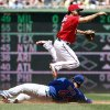Washington Nationals second baseman Anthony Rendon, top, jumps over Chicago Cubs\' Anthony Rizzo, who was out, but is unable to get Cubs\' Starlin Castro out at first base during the third inning of a baseball game at Nationals Park, Sunday, July 6, 2014, in Washington. (AP Photo/Alex Brandon)