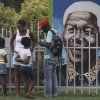 Visitors gather in front of a portrait of former president Nelson Mandela, in a Park in Soweto, South Africa, Thursday, March, 28, 2013. 94-year-old Mandela, the anti-apartheid leader who became South Africa\'s first black president, has been hit by a lung infection again and is in a hospital, the presidency said. Mandela, has become increasingly frail in recent years and has been hospitalized several times in recent months, including earlier this month when he underwent what authorities said was a scheduled medical test. The Nobel laureate is a revered figure in South Africa, which has honored his legacy of reconciliation by naming buildings and other places after him and printing his image on national banknotes. (AP Photo/Denis Farrell)