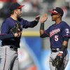Minnesota Twins closing pitcher Glen Perkins left, celebrates with teammate Eduardo Escobar (5) after defeating the Chicago White Sox 5-3 in a baseball game in Chicago, April 21, 2013. (AP Photo/Paul Beaty)