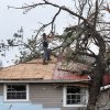 A man uses a chain saw to cut branches from a fallen tree on the roof of this home on US 177 north of I-40. A tornado caused extensive damage along I-40 at the junction with US 177 on the west side of Shawnee Sunday evening, May 19, 2013. Photo by Jim Beckel, The Oklahoman.