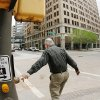 Photo - DOWNTOWN STREETS: A man presses the button for crosswalk as he walks across the street on Robinson at Main Street in downtown Oklahoma City  Thursday,  March 19, 2009.   BY JIM BECKEL, THE OKLAHOMAN ORG XMIT: KOD