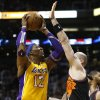 Los Angeles Lakers\' Dwight Howard (12) shoots over Phoenix Suns\' Marcin Gortat during the first half of an NBA basketball game, Wednesday, Jan. 30, 2013, in Phoenix. (AP Photo/Matt York)
