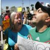 Photo - An unidentified protester, left, argues with American citizen Lupillo Rivera, brother of Mexican-American singer Jenni Rivera, right, as three buses carrying 140 immigrants attempt to enter the Murrieta U.S. Border Patrol station for processing on Tuesday, July 1, 2014.  (AP Photo/The Press-Enterprise, )  MAGS OUT; MANDATORY CREDIT