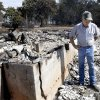Doug Roberson looks over damage at the home of Oscar Montelongo, Sunday, Aug. 5, 2012, in Glencoe, Okla., after wildfires moved through the area Saturday.