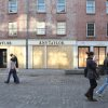 In this Friday, Nov. 23, 2012 photo, people walk past boarded up shops at New York\'s South Street Seaport. The South Street Seaport, a popular tourist destination, remains a ghost town since Superstorm Sandy. (AP Photo/Tina Fineberg)