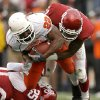 Dantrell Savage of OSU is brought down by D.J. Wolfe, left, and Lendy Holmes of OU during the first half of the college football game between the University of Oklahoma Sooners (OU) and the Oklahoma State University Cowboys (OSU) at the Gaylord Family-Memorial Stadium on Saturday, Nov. 24, 2007, in Norman, Okla. Photo By Bryan Terry, The Oklahoman