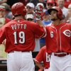 Photo - Cincinnati Reds' Joey Votto (19) is congratulated by Billy Hamilton (6) after Votto hit a two-run home run off Tampa Bay Rays starting pitcher Cesar Ramos in the third inning of a baseball game, Sunday, April 13, 2014, in Cincinnati. (AP Photo/Al Behrman)