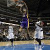 Los Angeles Lakers\' Robert Sacre (50) goes up for an uncontested dunk as Dallas Mavericks\' Monta Ellis (11) and DeJuan Blair, right, watch in the first half of an NBA basketball game, Tuesday, Jan. 7, 2014, in Dallas. (AP Photo/Tony Gutierrez)