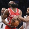 Photo - Houston Rockets guard James Harden (13) is fouled by Brooklyn Nets forward Alan Anderson, right, as center Andray Blatche (0) looks on during the second half of their NBA basketball game at the Barclays Center, Tuesday, April 1, 2014, in New York. (AP Photo/John Minchillo)