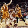Oklahoma Sooner Jordan Woodard (10) tries to go between Texas Longhorns Javan Felix (3) and Jonathan Holmes (10) as the University of Oklahoma Sooners (OU) men play the Texas Longhorns (TU) in NCAA, college basketball at The Lloyd Noble Center on Saturday, March 1, 2014 in Norman, Okla. Photo by Steve Sisney, The Oklahoman
