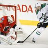 Dallas Stars\' Rich Peverley, right, tries to get the puck past Calgary Flames goalie Reto Berra, from Switzerland, during first-period NHL hockey game action in Calgary, Alberta., Thursday, Nov. 14, 2013. (AP Photo/The Canadian Press, Jeff McIntosh)