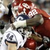 Oklahoma\'s Stacy McGee (92), top, and Oklahoma\'s Tom Wort (21) bring down Connecticut\'s Robbie Frey (44) during the Fiesta Bowl college football game between the University of Oklahoma Sooners and the University of Connecticut Huskies in Glendale, Ariz., at the University of Phoenix Stadium on Saturday, Jan. 1, 2011. Photo by Bryan Terry, The Oklahoman
