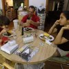 Photo - In this Friday, June 14, 2013 photo, Karl Owen has lunch with his children Marcus, left, and Jordan in their Chapel Hill, N.C. home. Owen lost his wife and the mother of their two children to cancer three years ago. (AP Photo/Gerry Broome)