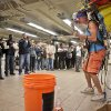 "Photo - In this Wednesday, Oct. 9, 2013, photo, subway riders pause to listen as Jeffrey Masin, right, performs his one-man band ensemble at a subway platform at Union Square station in New York. Masin, from Waterford, Conn., has performed his one-man band show he calls ""Jumping Jam Band"" since 1979, traveling across the U.S. and Europe.  A street musician mostly, he started performing legally  at subway stations more than a year ago and it's been ""very good.""  (AP Photo/Bebeto Matthews)"