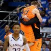 Oklahoma State\'s Markel Brown, left rear, and Phil Forte, who was jumping into the arms of a teammate after the final buzzer sounded on the Cowboys\' 85-80 upset win over Ben McLemore (23) and Kansas at Allen Fieldhouse in Lawrence, Kansas, on Saturday, February 2, 2013. (Rich Sugg/Kansas City Star/MCT)