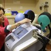 Photo - In this Wednesday, July 10, 2013 photo, Dr. Hope Rugo, an oncologist and breast cancer specialist, demonstrates the use of a Dignitana DigniCap system at the University of California San Francisco Mount Zion Hospital cancer center in San Francisco. The caps chill the head and scalp allowing for hair preservation in chemo treatments. (AP Photo/Eric Risberg)