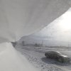 Snowy peak looming over the road as a car goes through the blizzard on the outskirts of Minsk, Belarus, Saturday, March 16, 2013. (AP Photo/Sergei Grits)