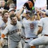 Photo - Texas players greet C.J Hinojosa (9) to the dugout after he hit a home run against UC Irvine in the seventh inning of an NCAA baseball College World Series elimination game in Omaha, Neb., Wednesday, June 18, 2014. (AP Photo/Eric Francis)