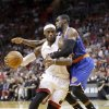 Photo - Miami Heat forward LeBron James is fouled by New York Knicks guard Tim Hardaway Jr., right, during the first half of an NBA basketball game, Sunday, April 6, 2014, in Miami. (AP Photo/Wilfredo Lee)